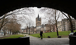 """Cologne, Germany, Jan. 2012 -  Pedestrians, framed by the arches of the Hohenzollern bridge, make their way along the Rhein River Promenade, in the shadow of the Great St. Martin's church, in the """"Old Town"""" district of Cologne, Germany. (Photo © Jock Fistick)."""