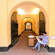 A guard sits at the main entrance of Hoa Lo Prison museum collecting tickets from visitors. Hoa Lo Prison, also known sarcastically as the Hanoi Hilton during the Vietnam War, was originally a French colonial prison for political prisoners and then a North Vietnamese prison for prisoners of war. It is especially famous for being the jail used for American pilots shot down during the Vietnam War.