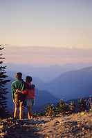 A couple relaxes by the trail, Whistler mountain summer evening.