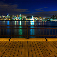 An urban lakeside scene at night from a wooden jetty