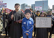 People personating President Park Geun-Hye (2nd R) and justices (R and 3rd R) of the Constitutional Court, march toward presidential Blue House in Seoul, South Korea, Mar 10, 2017, after the court upheld the impeachment of President Park. The court's eight justices unanimously ruled against her and Park became the first president ousted in South Korea. Park was impeached by the national assembly last December for allegedly letting her long time friend Choi Soon-sil meddle in state affairs and colluding with her to extort millions of dollars from chaebols, including Samsung. Photo by Lee Jae-Won (SOUTH KOREA) www.leejaewonpix.com
