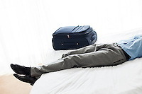 Low section of businessman sleeping beside luggage in hotel room