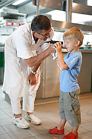 Three Star Michelin Restaurant Michel Bras in Laguiole, Aveyron regoin of southwest France..Chef Michel Bras shows his grand children how to check the sugar content of a tomato..August 2008