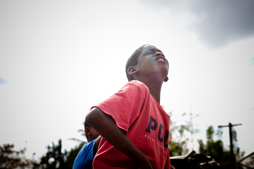 A boy watches a high fly ball sail into the outfield during batting practice for the Warriors baseball team on Thursday, February 25, 2010 in San Antonio de Guerra, Dominican Republic.