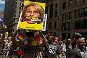 "New York, NY - 25 June 2017. New York City Heritage of Pride March filled Fifth Avenue for hours with groups from the LGBT community and it's supporters. A large contingent of marchers from Rise and Resist, many of whom were carrying signs, the largest of which here has a large photo of  Secretary of Education Betsy DeVos, with the banner ""Betsy DeVos / Queer Basher"" superimposed over her mouth."