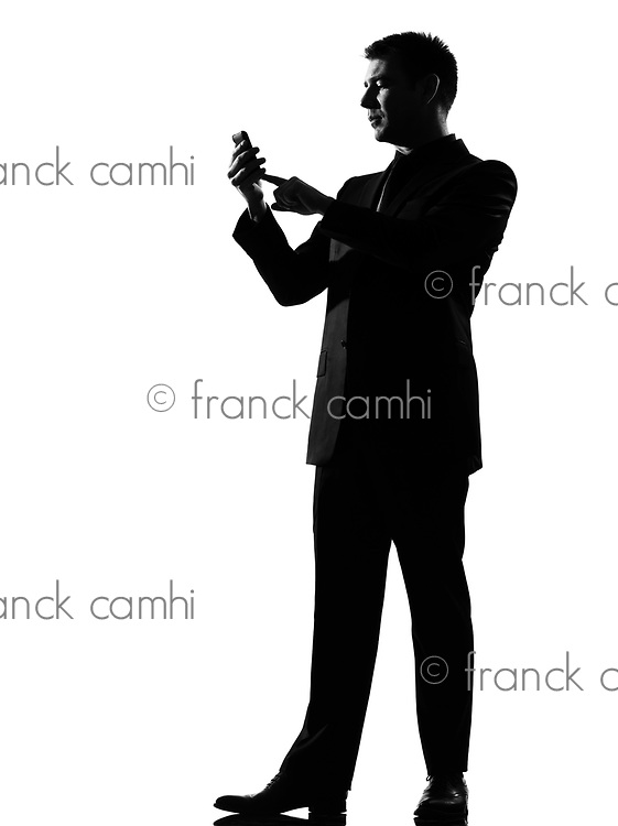 silhouette caucasian business man on the phone  sms text messaging full length on studio isolated white background