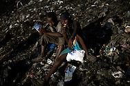 Boys eat food found in the trash as residents sort through garbage to find recyclable items to sell at the Dandora Municipal Dumping Site in Nairobi, Kenya June 29, 2008. Scavengers search for items to sell such a metal and plastic bottles which sell for roughly half a dollar per kilogram. Daily over 2000 tons of garbage are delivered to the site which a 2007 study commissioned by the U.N. Environment Program found that half of 328 children tested round the site had lead concentrations in their blood exceeding the internationally accepted level..