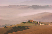 A rural farmhouse atop a hill backed by misty hills near Pienza, Italy. (between Rome and Florence, near Montepulciano).