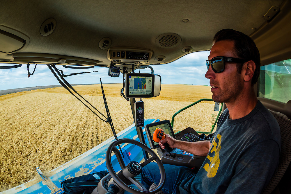 A farmer in the cab of his state of the art combine harvestor whcih uses GPS and automation to increase the efficiency of the wheat harvest, Schields & Sons Farming, Goodland, Kansas USA.