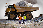 Mine worker Mahmoud Nanga (right) and a co-worker (name unknown) watch as a large truck gets loaded with ore in the main pit of the Youga gold mine near the town of Youga, approximately 205 km southeast of Burkina Faso's capital Ouagadougou on Tuesday April 28, 2009.