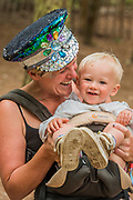 A mother in a homemade hat enjoying the woods with her baby - The 2017 Latitude Festival, Henham Park. Suffolk 15 July 2017