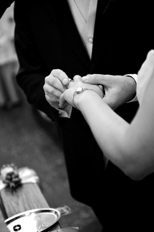 Der Bräutigam steckt während der Trauungszeremonie den Ring an den Finger der Braut