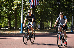 © Licensed to London News Pictures. 23/07/2018. London, UK. Two men ride their bikes along The Mall in front of Buckingham Palace in early morning sun in central London, as the hot weather continues in the capital. Forecasters are predicting record temperatures this week. Photo credit: Ben Cawthra/LNP