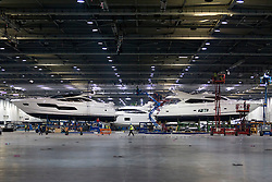 © Licensed to London News Pictures. 22/12/2012. London, UK. A Sunseeker 80 Yacht (R) and a Sunseeker 80 Predator (R) are seen amongst workmen as preparations for the 2013 Tullett Prebon London Boat Show take place at London's Excel Centre today (22/12/12). The show runs from 12th to the 20th of January 2013. Photo credit: Matt Cetti-Roberts/LNP
