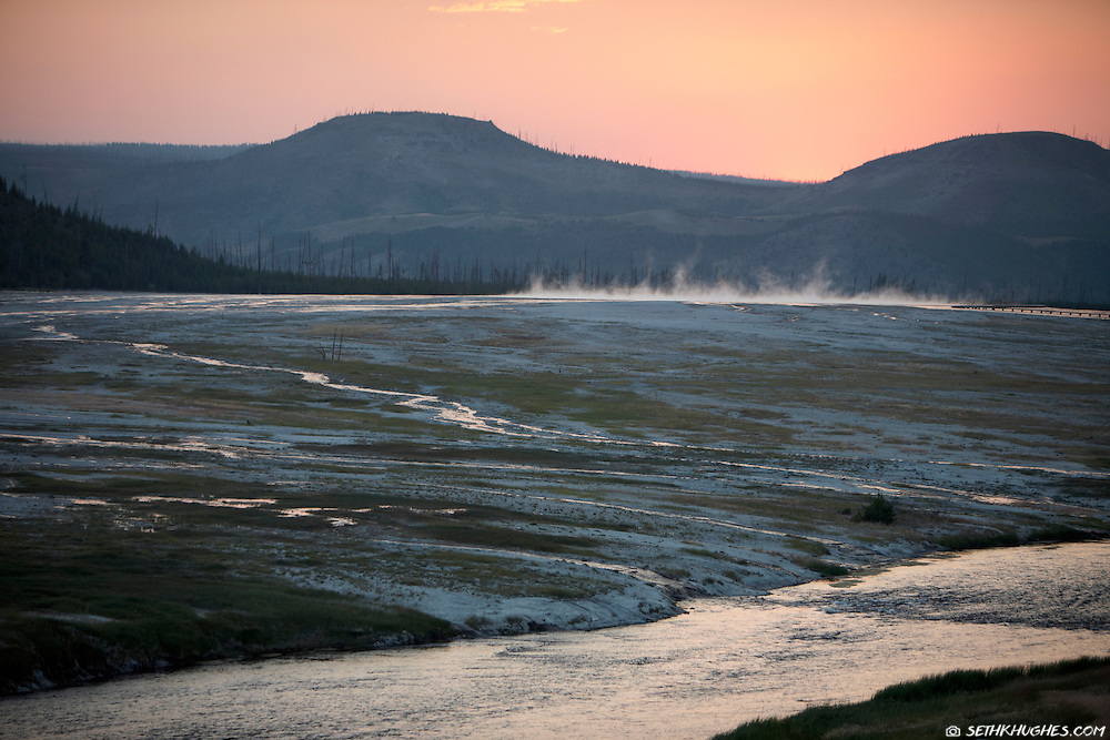 The sun sets over the Midway Geyser Basin and the Firehole River in Yellowstone National Park.