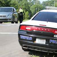 Tupelo Police Officer Mitchell Cunningham checks for driver license's and properly tags during a safety checkpoint on Lumpkin Street.