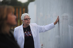 Mirah Sinoply,of Johnstown, Pa., pauses and touches the name of every person listed while she walks along the memorial wall at the Flight 93 National Memorial in Shanksville, Pa. Saturday, Sept. 10, 2011. Sinoply said she did not know any of the victims or members of their families but wanted to visit and pay tribute to those that were lost.