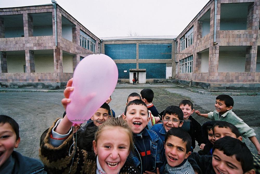 Ausgelassen fröhlich sind diese armenischen Kindergartenkinder. Doch nur noch wenige Kinder besuchen den grossen Kindergarten im armenischen Hoktember (hinten). Kindergarden kids enjoy a game with a pink ballon in village in Armenia.