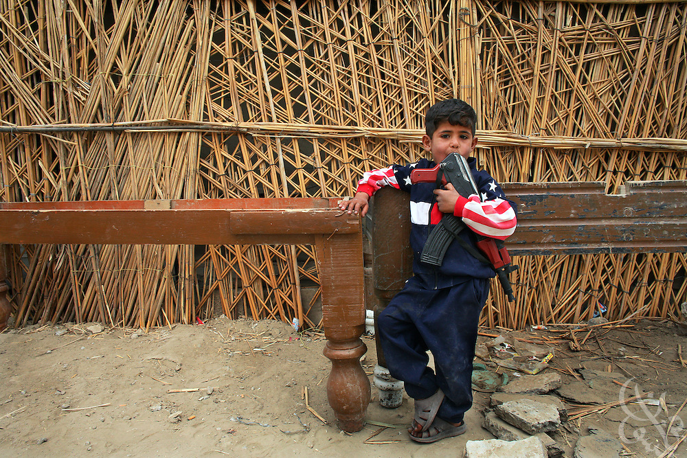 An Iraqi boy plays with a toy gun in a homeless community at an abandoned army base, Camp Rashid in Baghdad, Iraq Oct 23, 2006. Hundreds of Iraqi families who cannot afford elevated post war housing costs have taken up residence in the abandoned base, making do with what they can.