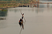 Mar. 13, 2009 -- VANG VIENG, LAOS: A man poles a customer across the Nam Xong River in Vieng Viang, Laos. Photo by Jack Kurtz
