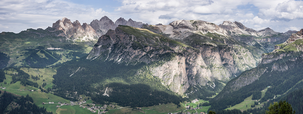 In Val Gardena (Gherdëina / Gröden), hike the gorgeous Vallunga/Langental valley in Puez-Geisler Nature Park, Dolomites, Italy, Europe. The beautiful ski resort of Selva di Val Gardena (German: Wolkenstein in Gröden; Ladin: Sëlva Gherdëine) makes a great hiking base in the Dolomites, in the South Tyrol region (Trentino-Alto Adige/Südtirol) of Italy, Europe. For our favorite hike in the Dolomiti, start from Selva with the first morning bus to Ortisei, take the Seceda lift (to the upper meadow at far left in photo), admire great views up at the cross on the edge of the next valley (Val di Funes/Villnöss), then walk 12 miles (2000 feet up, 5000 feet down) via the steep pass Furcela Forces De Sieles (Forcella Forces de Sielles) to beautiful Vallunga (trail #2 to 16), finishing where you started in Selva. The hike traverses the Geisler/Odle (back left) and Puez Groups (right) from verdant pastures to alpine wonders, all preserved in a vast Nature Park: Parco Naturale Puez-Odle (German: Naturpark Puez-Geisler; Ladin: Parch Natural Pöz-Odles). UNESCO honored the Dolomites as a natural World Heritage Site in 2009. This panorama was stitched from 3 overlapping photos.