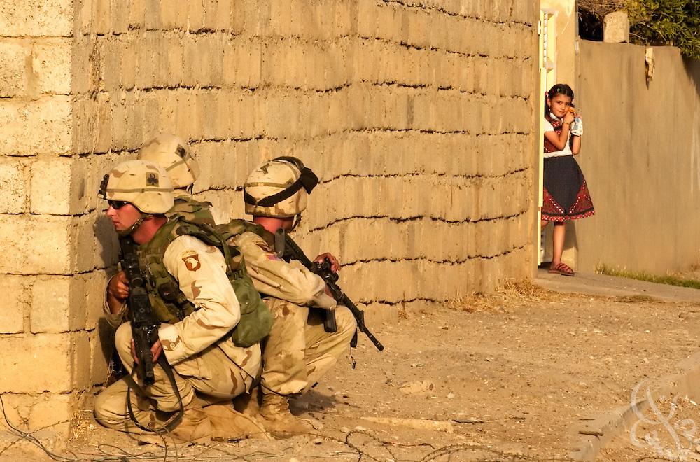A local Iraqi girl watches from the doorway of her home as U.S. Army 101st Airborne troops take cover July 23, 2003 near the site where they killed both Uday and Qusay Hussein in Mosul, Iraq the day before. The two sons of the former Iraqi leader Saddam Hussein were cornered in an affluent home in the northern city of Mosul and killed in what U.S. military officials described as a fierce firefight that lasted for several hours.