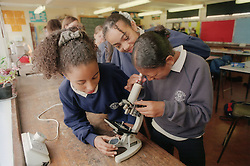 Group of secondary school pupils looking through microscope in classroom,