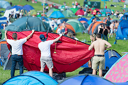 © Licensed to London News Pictures. 24/06/2015. Pilton, UK.   Festival goers at Glastonbury Festival set up their tents shortly after entering the site at 8am on  Wednesday Day 1 of the festival.        The pedestrian gates to the festival opened at 8am this morning, with many festival goers arriving and waiting throughout last night for the opening.  This years headline acts include Kanye West, The Who and Florence and the Machine, the latter having been upgraded in the bill to replace original headline act Foo Fighters.  Photo credit: Richard Isaac/LNP