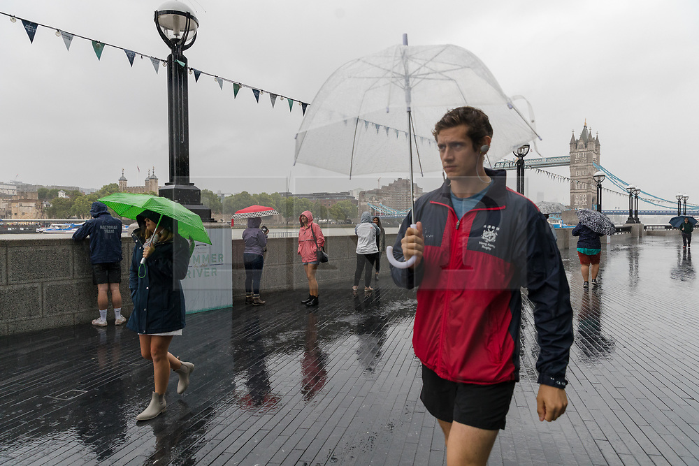 © Licensed to London News Pictures. 27/07/2019. London, UK. People with umbrellas walking near Tower Bridge during heavy rain this morning. London and the UK are experiencing heavy rain and stormy weather today following the heatwave and record temperatures during the week. Photo credit: Vickie Flores/LNP