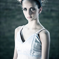Female youth with sad expression wearing white dress standing looking at camera