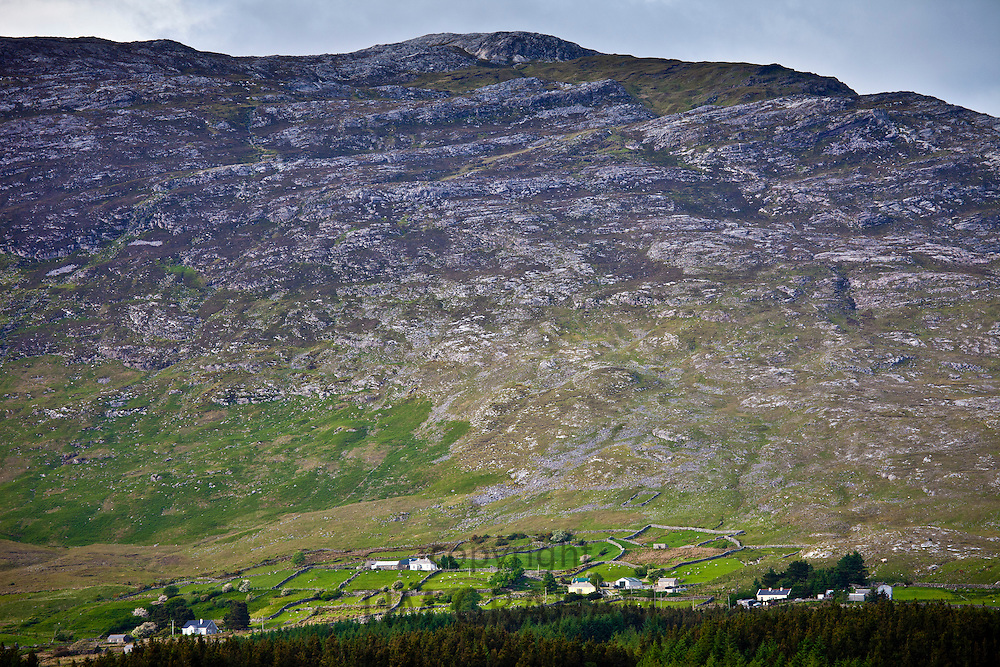 Homes nestling at the foot of the Maumturk mountain range near Recess in Connemara, County Galway, Ireland