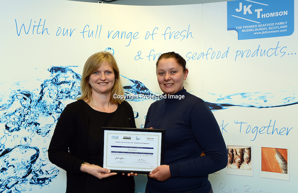 Scottish Apprenticeship Week 19-23 May 2014<br /> <br /> <br /> Seafood Apprentice Kirsty Peacock, 20, has been identified as the 3,000th person to complete a Scottish Modern Apprenticeship. She works for family seafood processing firm JK Thomson of Musselburgh, near Edinburgh<br /> Kirsty has completed  a Modern Apprenticeship L2 in  Fish & Shellfish Processing skills.  She is one of a number  (33 candidates have achieved a modern apprenticeships along with 2 trained and qualified assessors  with a further 29 currently working towards level 2MA and 2 L3 first in Scotland to be working towards level 2  MA and and 2 L3 first in Scotland to be working towards the new Level 3 in Fish and Shellfish industry skills.<br /> <br /> Pictured: Kirsty Peacock, (right)  3000th Food & Drink Manufacturing Modern Apprentice receives her certificate from Justine Fosh, CEO, Improve, Skills Council for UK Food & Drink manufacturing industry.