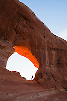 A woman climbing up into Looking Glass Arch on Looking Glass Rock in Southeast Utah, USA.