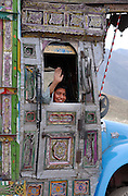 Afghan boy waving from an elaborately decorated truck on the road between Jalalabad and Kabul, Afghanistan. 2002.
