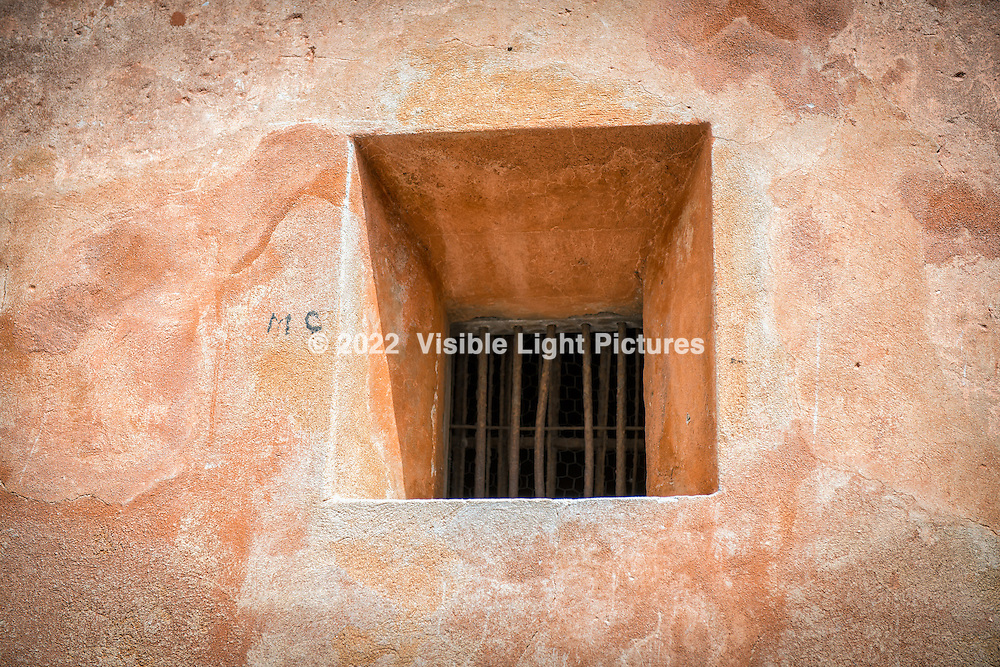 Window with bars on a terra cotta colored building in the South of France.