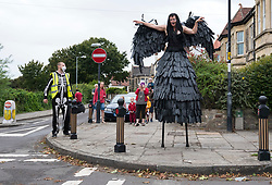 © Licensed to London News Pictures; 26/07/2020; Bristol, UK. Corvid19 the Crow and the Zebra perform on stilts in the streets of Totterdown in The Bristol Coddywomple.  The Bristol Coddywomple is an ambling celebration of street performance with more than 40 performance artists, entertainers and musicians taking ambling versions of their shows out into their local areas, giving them a chance to show off their talents to live audiences while venues remain shut due to the coronavirus Covid-19 pandemic and lockdown when much art and performance has been unable to take place in normal venues. This is the first one of its kind in the UK, with the Coddywomplers performers of many types performing on the streets following pre-mapped and publicised routes to entertain their neighbours as they pass through with music, circus and visual treats. Audiences can watch from their windows and doorways, or come outside to interact with the entertainers from their front yards. Photo credit: Simon Chapman/LNP.