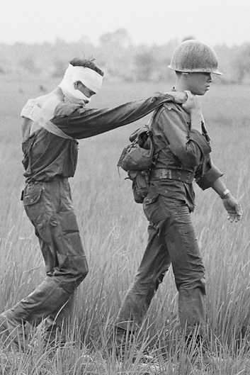 South Vietnamese soldier leads wounded buddy to safety after military operation in the Delta region of South Vietnam during the Vietnam War.
