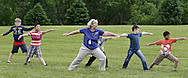 Bethel Woods Center for the Arts volunteer Linda Pomes leads students from Anna S. Kuhl Elementary School in Port Jervis in yoga on the festival field on Thursday, June 6, 2013.