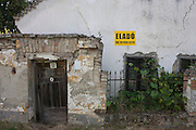 An abandoned, crumbling and riuned house with its accompanying land, has the Hungarian word Elado - meaning For Sale - on a cracked exterior wall in a village of (population 178) on 26th June 2016, in Bakonygyirot, Gyor-Moson-Sopron, Hungary. Its doorway is warped and leaning, the brickwork is crumbling and in a general poor condition. As the old pass away, so properties in the rural backwaters of Hungary fail to regenerate a younger population and old, communist-era buildings are falling into disrepair. (Photo by Richard Baker / In Pictures via Getty Images)