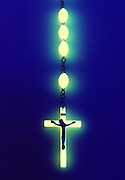 Glowing rosary against dark background.Black light