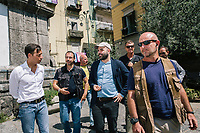 """NAPLES, ITALY - 30 JULY 2018: Roberto Saviano (center), an Italian journalist, writer and essayist is seen here with his police escort in the Sanità neighborhood, where in 2017 the 17-year-old innocent victim Genny Cesarano was shot and killed by stray bullet  in cross fire between 2 rival gangs vying for territorial control, in Naples, Italy, on July 30th 2018.<br /> <br /> The  isolation of the neighborhood Sanità over the years provided an ideal location for the Camorra to expand their illicit activities and profit from soaring unemployment rates and economic instability,<br /> <br /> After the first death threats of 2006 by the Casalese clan , a cartel of the Camorra, which he denounced in his exposé and in the piazza of Casal di Principe during a demonstration in defense of legality, Roberto Saviano was put under a strict security protocol. Since 2006 Roberto Saviano has lived under police protection.<br /> <br /> Saviano's latest novel """"The Piranhas"""", which tells the story of the rise of  a paranza (or Children's gang) and it leader Nicolas, will be released in the United States on September 4th 2018."""