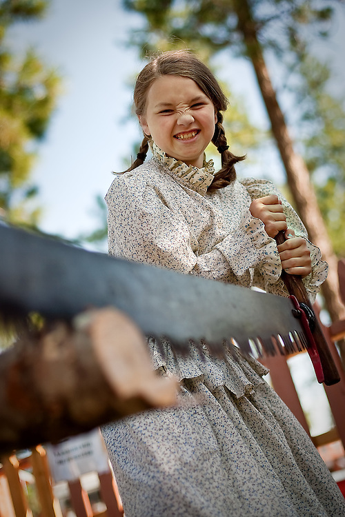JEROME A. POLLOS/Press..Jensyn Harmon, 10, learns first-hand how difficult it was to be prepare logs for homebuilding at Ponderosa Elementary's Rendezvous Days held Thursday. Students toured and participated in various stations featuring archery, cast iron cooking, forestry, cavalry and artillery, Native American living and were given a ride on a horse and buggy.
