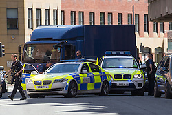 © Licensed to London News Pictures . 14/05/2014 . Leeds , UK . A multi-vehicle armed police escort from City of London Police , escorting plain blue lorries to Bank House on Park Place in Leeds today (Wednesday 14th May 2014) . Armed police with sirens sounding blocked both ends of Park Place before two blue lorries , escorted by the police , reversed in to a garage in Bank House . The building is home to AXA Insurance amongst other businesses and the loading entrance is not visible on Google Street View maps but all surrounding buildings are . Photo credit : Joel Goodman/LNP