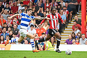 Brentford Midfielder Romaine Sawyers (19) and Queens Park Rangers Midfielder Pawel Wszolek (22) battle for the ball during the EFL Sky Bet Championship match between Brentford and Queens Park Rangers at Griffin Park, London, England on 21 April 2018. Picture by Stephen Wright.