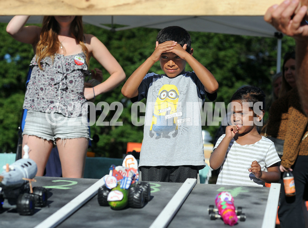 Kabi Shah (center), 7 and Syra Shah (right), 3 of Langhorne, Pennsylvania watch as their cars speed down the track during the zucchini races at Lower Makefield Farmer Market Thursday August 13, 2015 in Lower Makefield, Pennsylvania. Participants can create race cars out of zucchinis by poking holes into the veggies to put in axles made out of items like toothpicks or wooden skewers, the organizers said. Wheels, made out of any type of material, can be attached to the axles. No motor cars or remote controls are allowed, according to organizers. (Photo by William Thomas Cain)