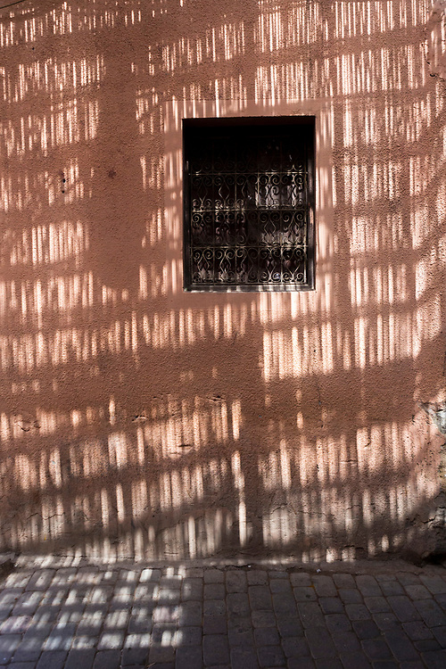 Shadows cast on the side of a building from sun shining through woven lattice roofing in the Marrakesh medina, Morocco