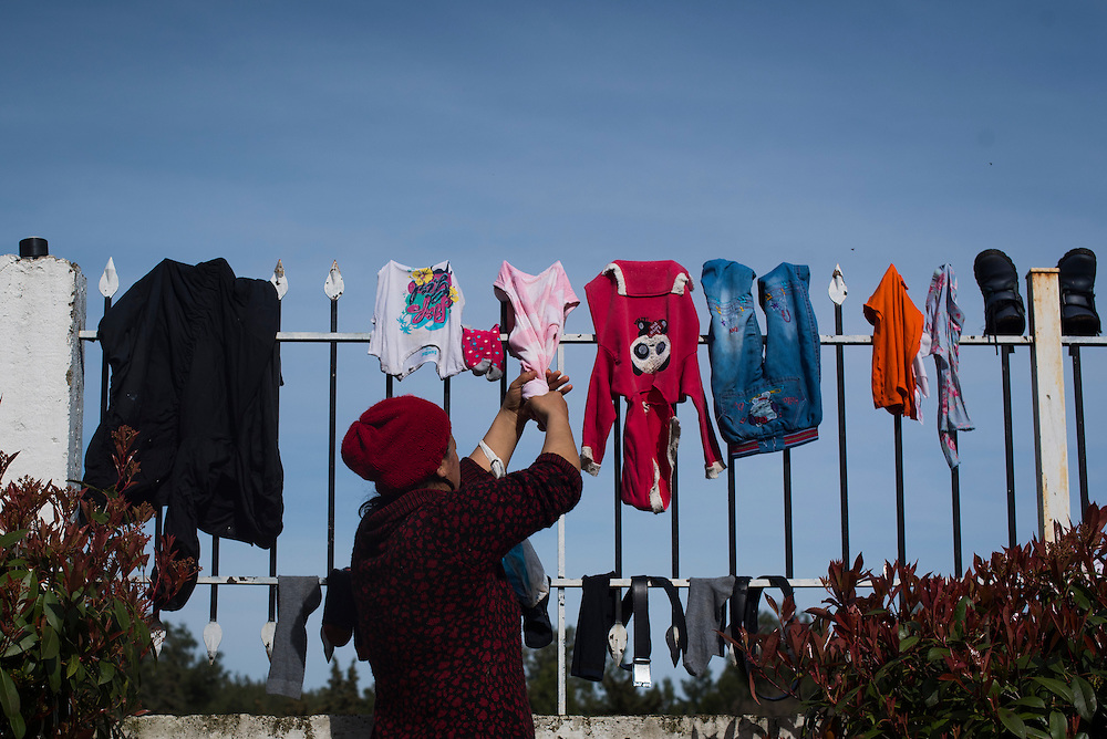 A woman dries clothes at a refugee camp near the Macedonian (FYROM) border on March 8, 2016 in Evzoni, Greece.