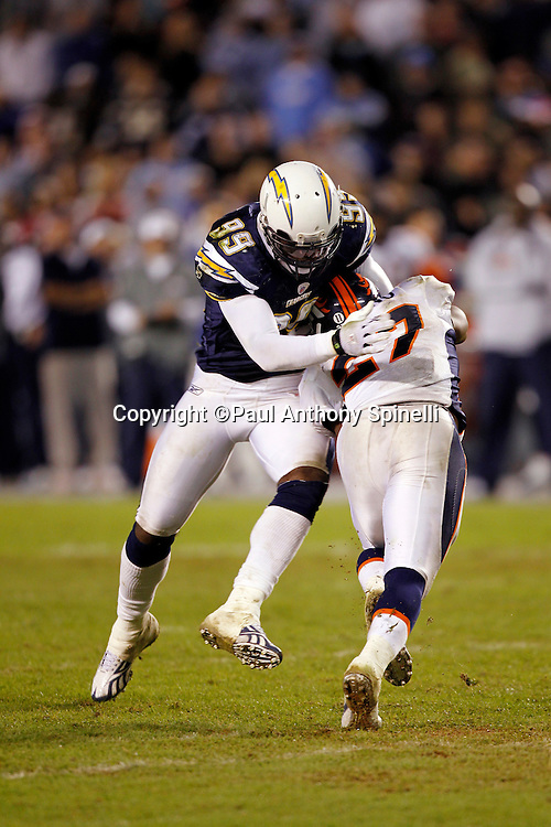 San Diego Chargers linebacker Kevin Burnett (99) stuffs a run by Denver Broncos running back Knowshon Moreno (27) during the fourth quarter of the NFL week 11 football game against the Denver Broncos on Monday, November 22, 2010 in San Diego, California. The Chargers won the game 35-14. (©Paul Anthony Spinelli)