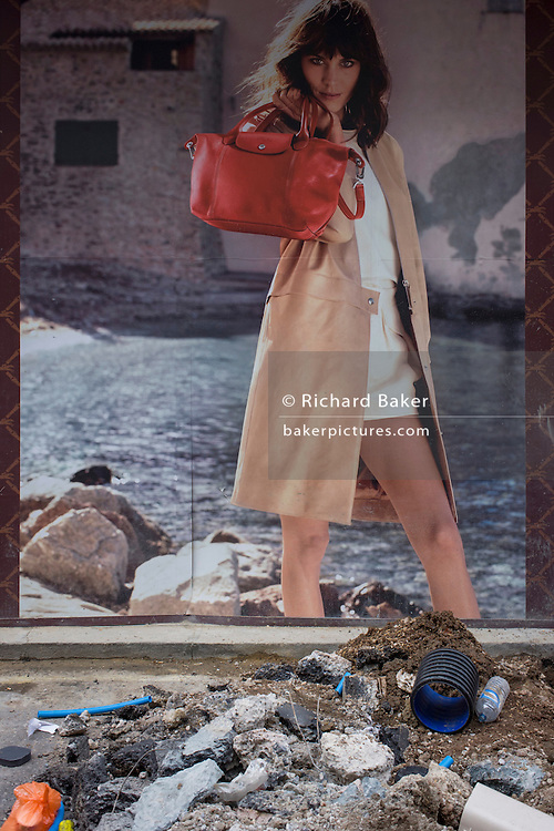 Fashion poster of a woman model with rocky environment and nearby roadworks mess in a central London street.