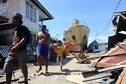 Oct. 5, 2018 - Donggala, Indonesia - People walk beneath the shadow of a ship washed into the street after the tsunami, while they search for salvageable items among the debris of a house in Donggala, Central Sulawesi. The death toll from Indonesia's multiple earthquakes and an ensuing tsunami jumped to 1,571, while search and rescue for the victims was extended. <br />